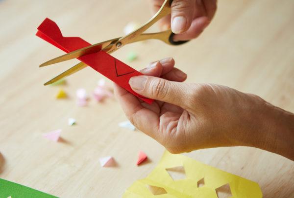 縦長にカットした折り紙を横方向に3回折った後、片側に切り込みを入れます。広げたらどんな形になるか、子供と楽しみながら作ってみて。