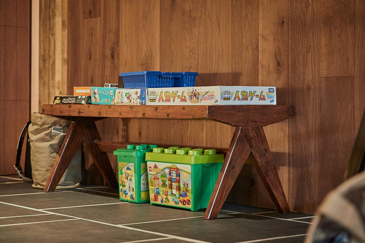 おもちゃの置かれたピエール・ジャンヌレのベンチ。人生ゲーム、オセロやマスターチェスはいつでも遊べるように出している。「親子の時間をもっと持ちたいとおもって、親子で遊べるボードゲームをさまざま買い求めました。一緒にできるってすごく楽しいですね」(直子さん)