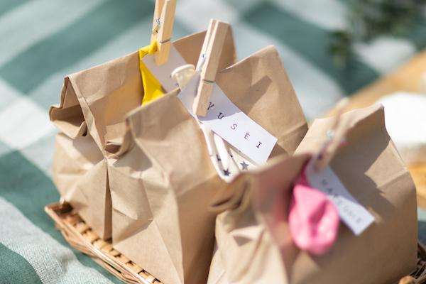 クラフトバッグに1人分のランチやお菓子を詰めたら、名前をスタンプした紙をウッドクリップで留めるだけ。写真のように風船も一緒につけてあげると、子供ウケは申し分なし。