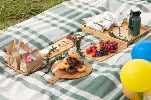 ピクニックラグの中央にトレイやカッティングボードをまとめれば、テーブルのような佇まいに。