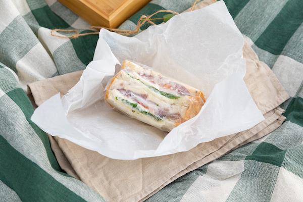 クッキングシートと麻紐でラッピングするだけで、サンドイッチもよそいき顔に。