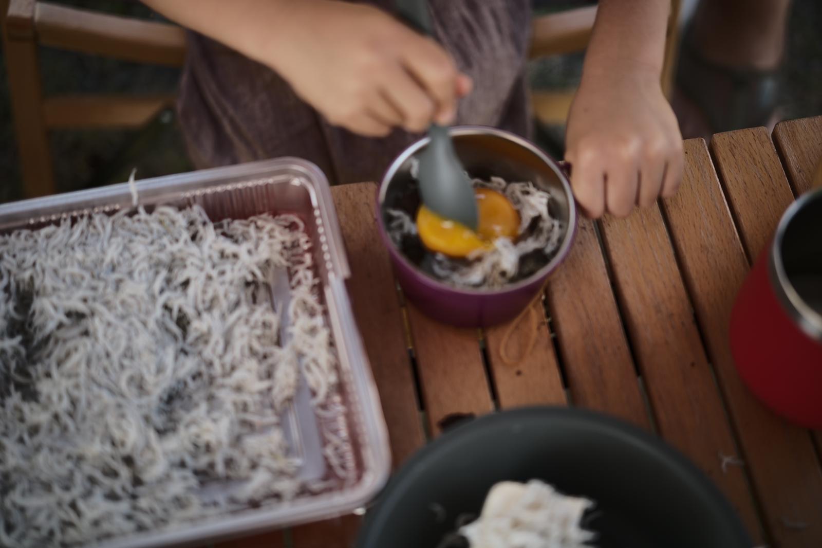 子どもがお手伝いしやすいように卵の黄身を殻に入れてスタンバイ。しらすと混ぜ混ぜしてもらいます。
