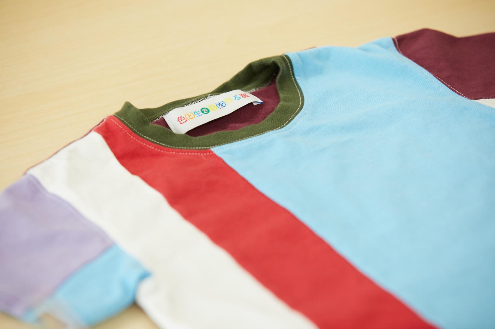 「色と生きるを作る服」のブランドタグもカラフルに