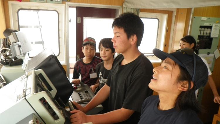 操舵室で操船する少年。HELLY HANSEN FAMILY VOYAGE