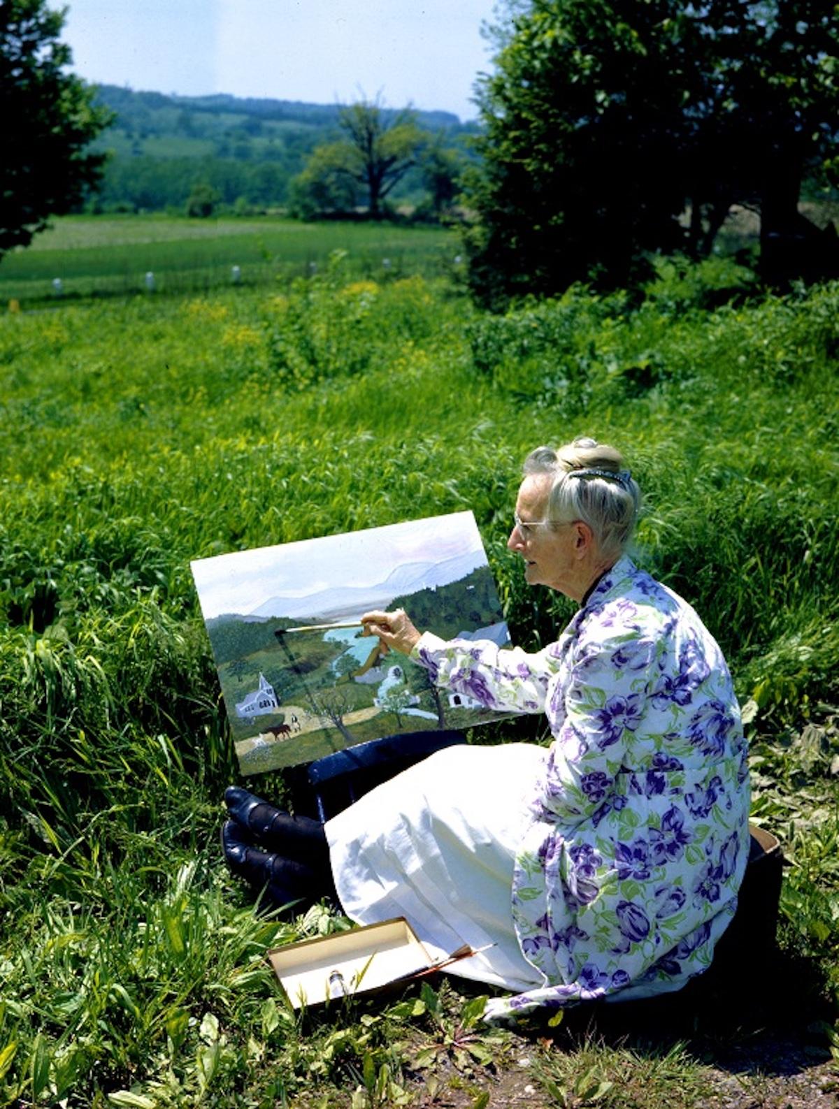 庭で絵を描くグランマ・モーゼス 1946年 写真:Ifor Thomas(ギャラリー・セント・エティエンヌ、ニューヨーク寄託) ©2021, Grandma Moses Properties Co., NY