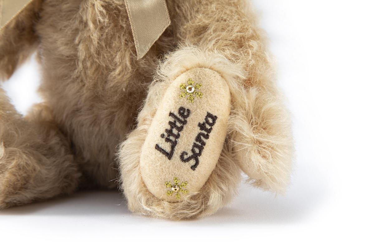 """ベアの足には、年号と雪の結晶、""""Little Santa""""の刺しゅうが。"""